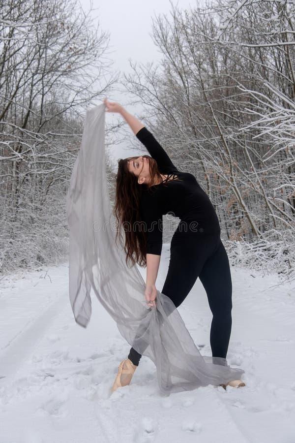 Den unga kvinnan i svart balettdräkt spelar i snöig skog med en ljus torkduk arkivbild
