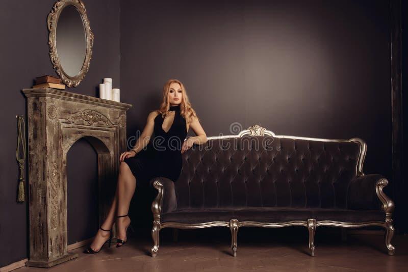 Den unga kvinnan i svart klänning sitter på soffan nära spisen royaltyfri fotografi