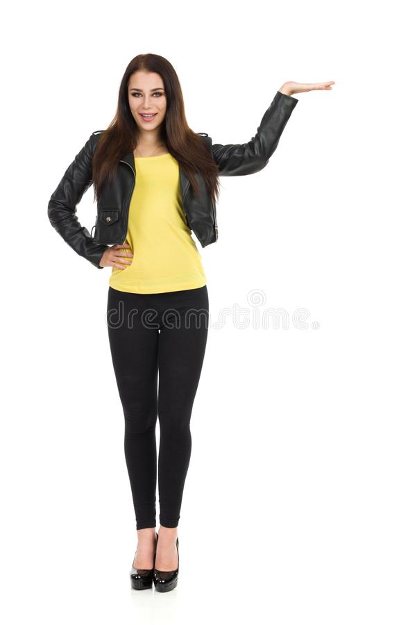 Den unga kvinnan i svart läderomslag, damasker och höga häl framlägger arkivbild