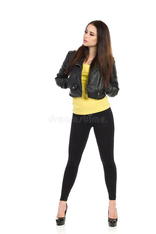 Den unga kvinnan i svart läderomslag, damasker och höga häl ser bort royaltyfri fotografi