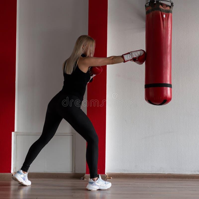 Den unga kvinnan i svart sportswear i stilfulla gymnastikskor i röda boxas handskar slår en stansa påse i en modern idrottshall F arkivbild