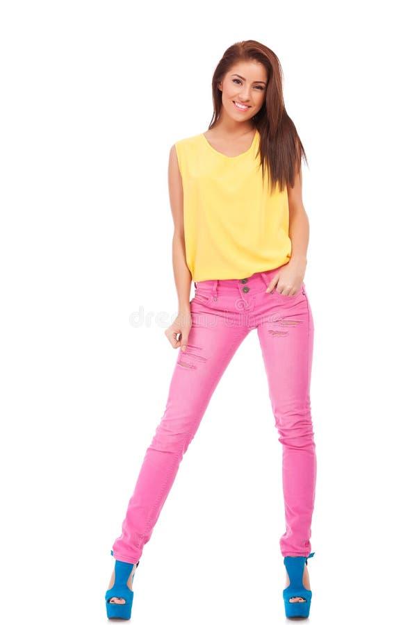 Den unga kvinnan i tillfällig kläder som är avkopplad poserar fotografering för bildbyråer