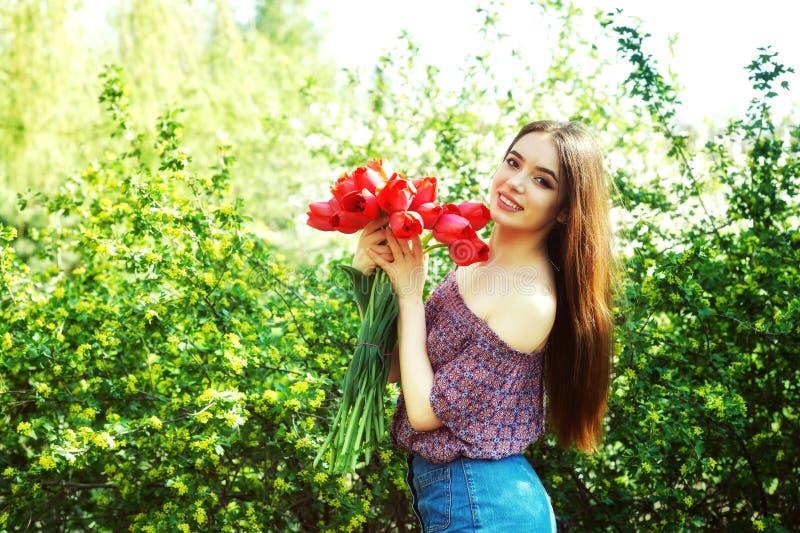 Den unga kvinnan i vår parkerar med tulpan fotografering för bildbyråer