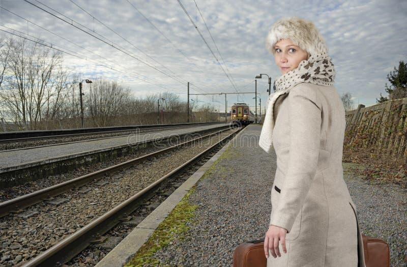 Den unga kvinnan i vinter beklär att vänta henne drevet royaltyfria bilder