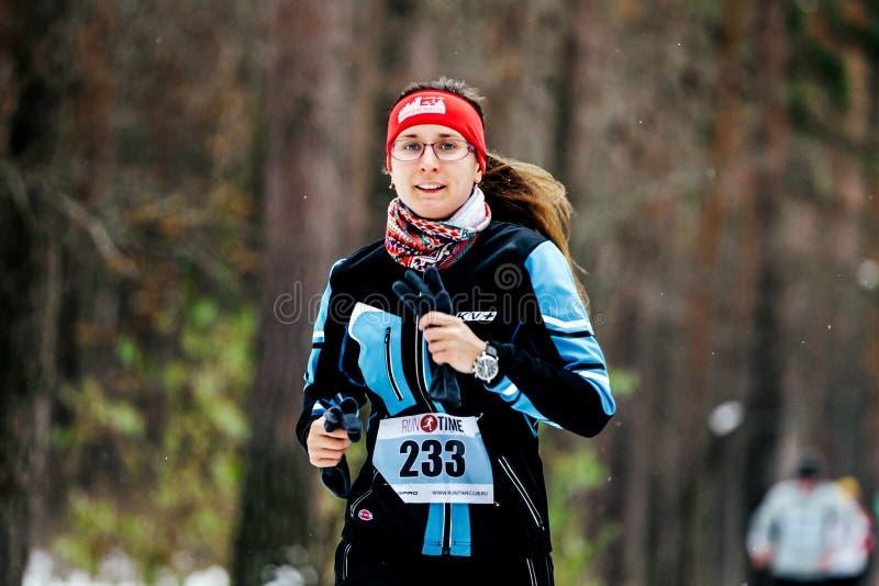 Den unga kvinnan i vintersport beklär den rinnande skogen royaltyfria bilder
