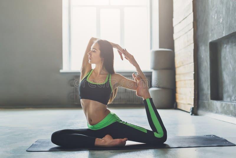 Den unga kvinnan i yogagrupp, sjöjungfru poserar asana arkivbilder