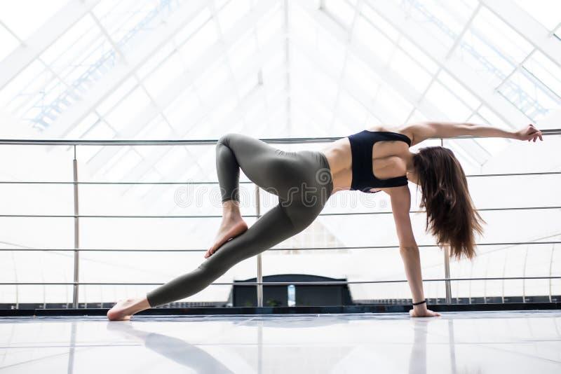 Den unga kvinnan i yogagrupp som gör härlig asana, övar Sund livsstil i konditionklubba Sträckning av asana fotografering för bildbyråer