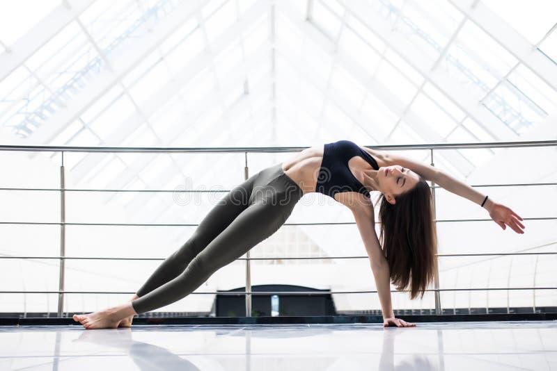 Den unga kvinnan i yogagrupp som gör härlig asana, övar Sund livsstil i konditionklubba Sträckning av yoga royaltyfri foto
