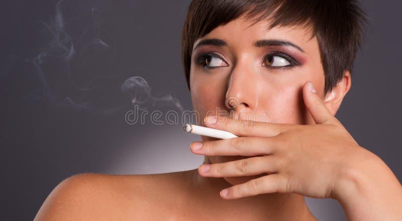 Den unga kvinnan inhalerar den intima rökareståenden för cigarettrök arkivbilder