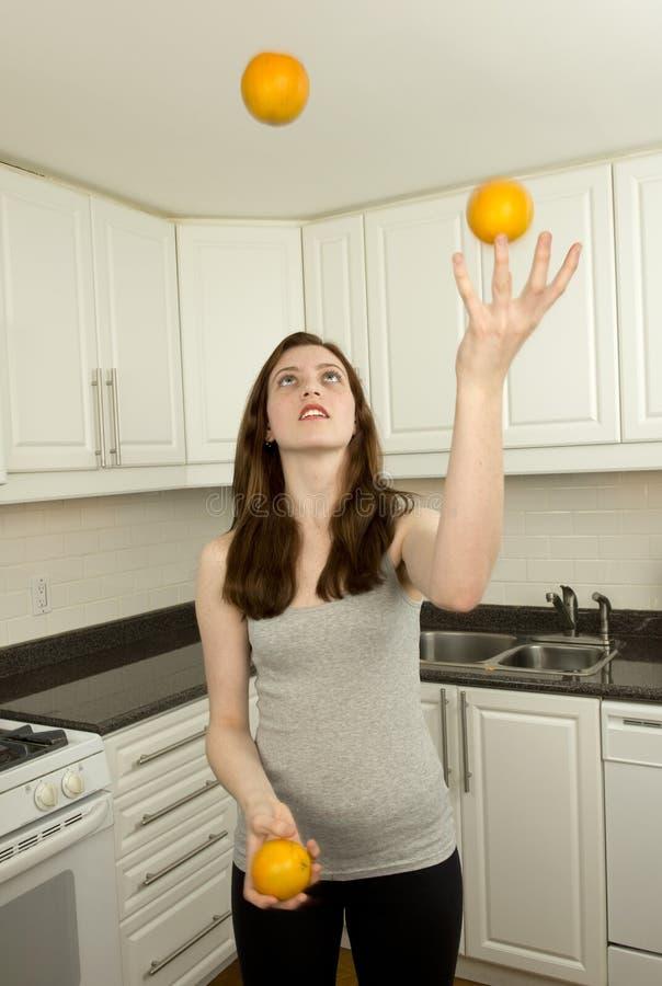 Den unga kvinnan jonglerar apelsin tre arkivfoto