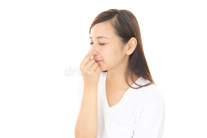 Den unga kvinnan klämmer hennes näsa arkivbild