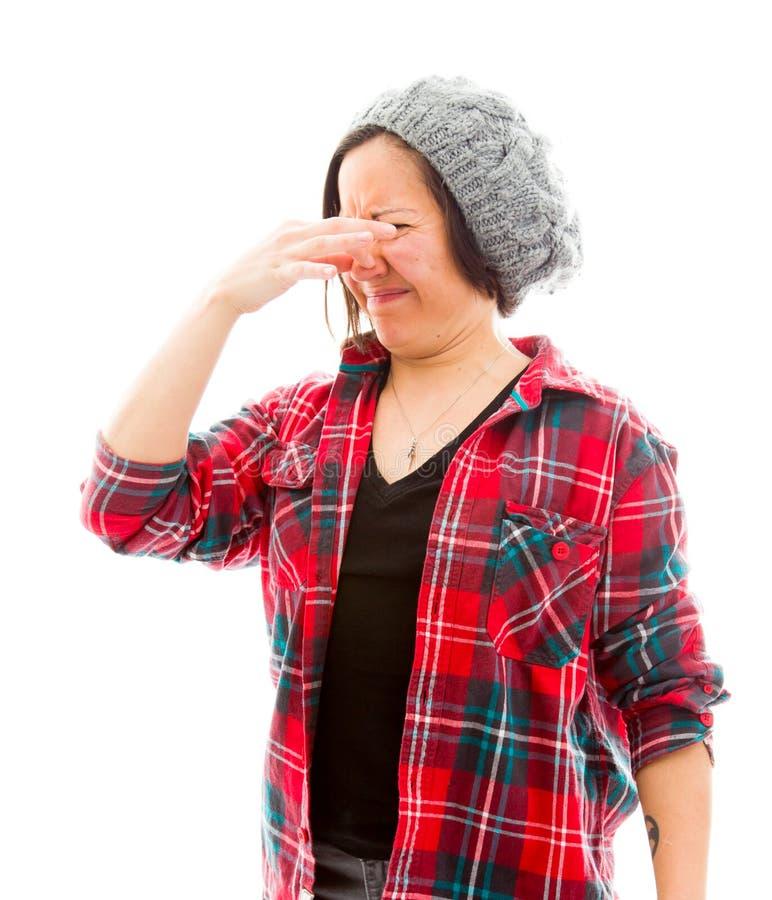 Den unga kvinnan klämmer hennes näsa fotografering för bildbyråer