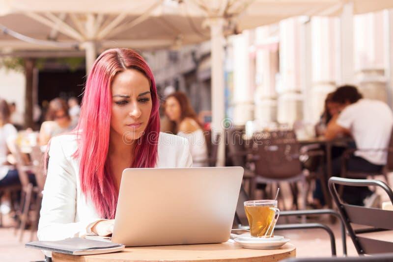 Den unga kvinnan koncentrerade genom att använda en bärbar dator på en tabell utanför en caf royaltyfri fotografi