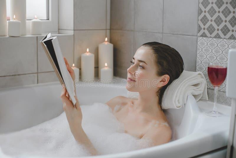 Den unga kvinnan kopplar av i ett varmt bad mycket av skum royaltyfri foto