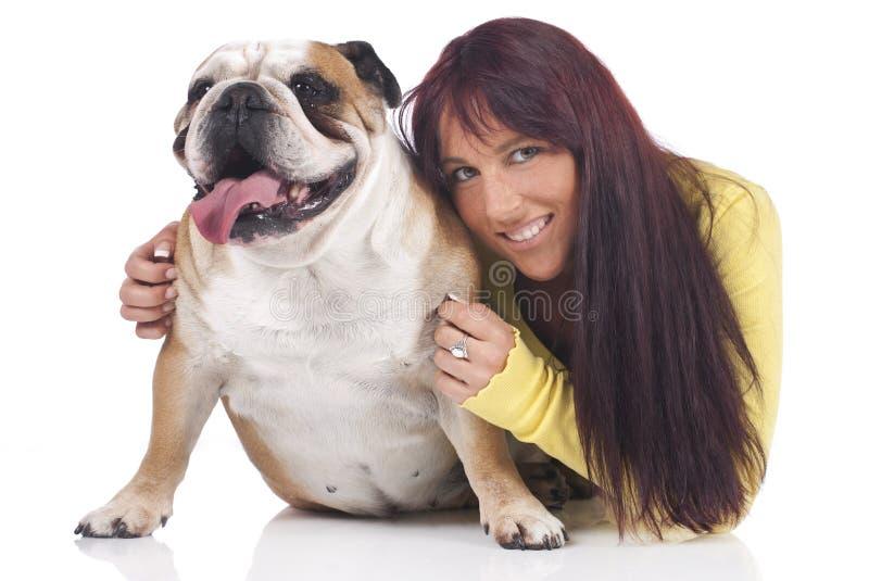 Den unga kvinnan kramar den engelska bulldoggen royaltyfria bilder