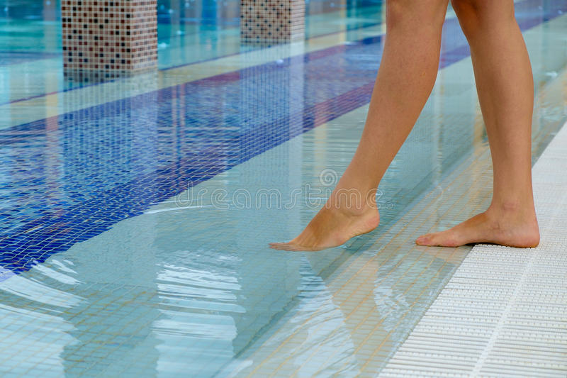 Den unga kvinnan lägger benen på ryggen anseende på kanten av en simbassäng och en avsmakning temperaturen av vattnet som doppar  arkivbilder