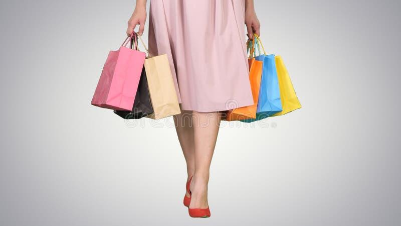 Den unga kvinnan lägger benen på ryggen bärande färgrika shoppa påsar på lutningbakgrund arkivfoton