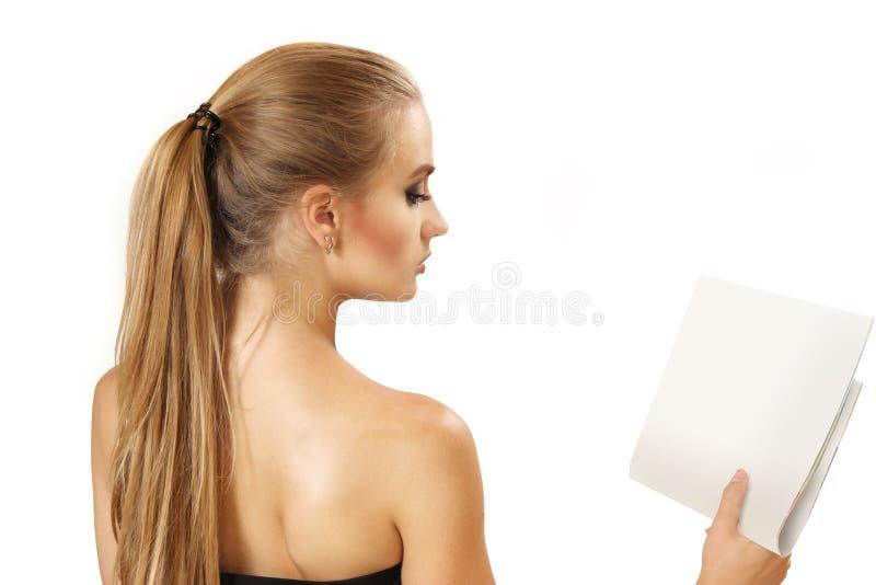 Den unga kvinnan läser tidningen fotografering för bildbyråer
