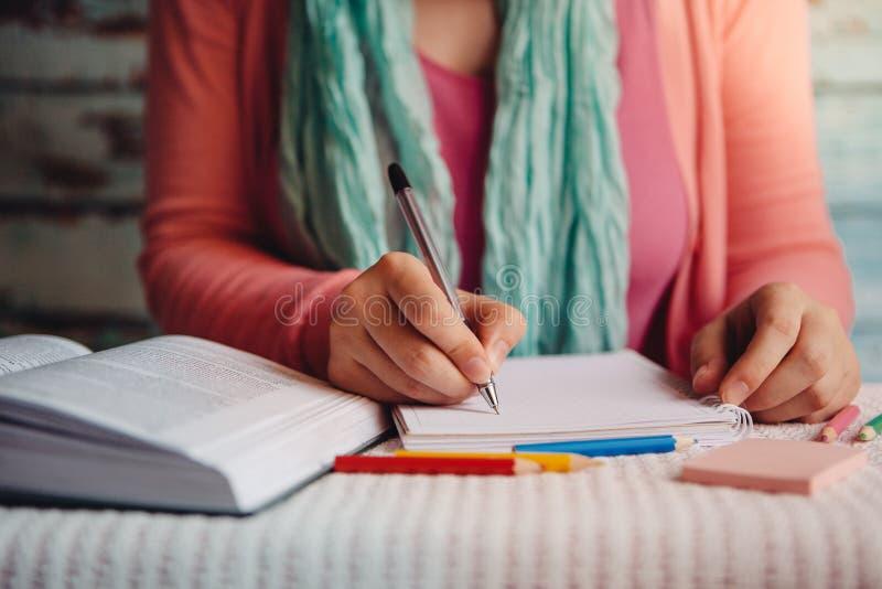 Den unga kvinnan läste och skriver, utbildnings- eller fritidbegreppet med studenten arkivbilder