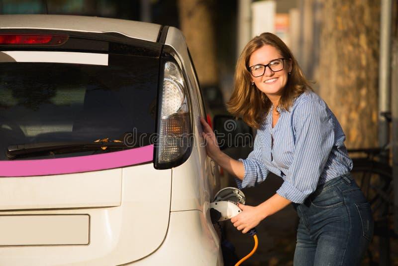 Den unga kvinnan laddar en elbil fotografering för bildbyråer