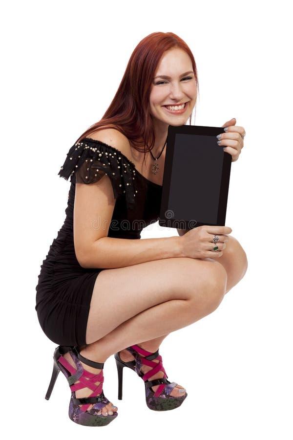Den unga kvinnan ler, medan rymma en tom minnestavladator. arkivbild