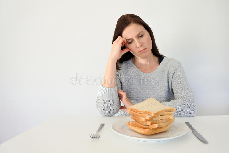 Den unga kvinnan lider från en gluten arkivbild