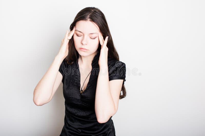 Den unga kvinnan lider fr?n en huvudv?rk St?ende av en flicka som griper hennes huvud Migr?n och blodtryckproblem arkivfoton