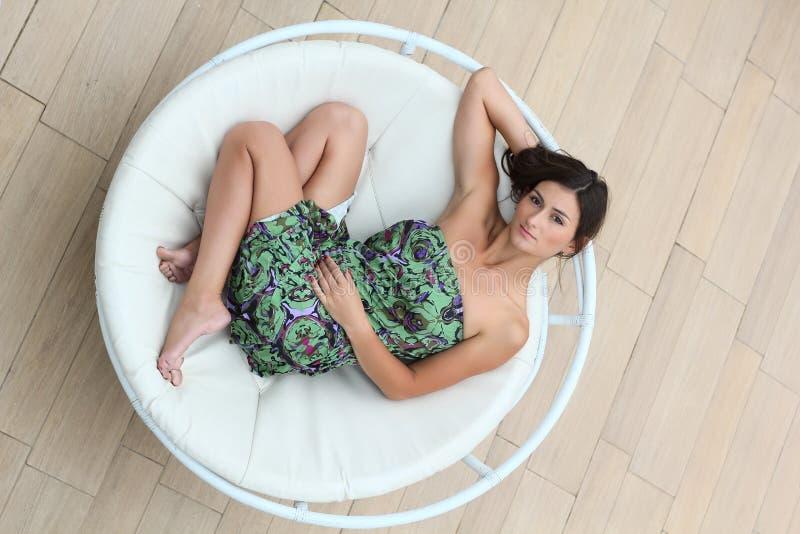 Den unga kvinnan ligger i cirkelchaisen-longue royaltyfria foton