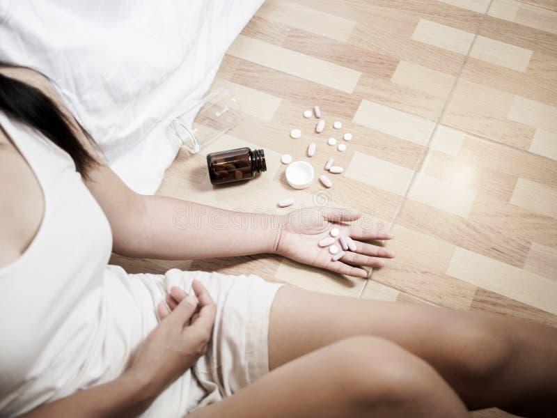 Den unga kvinnan ligger på golvet med många preventivpillerar arkivfoto