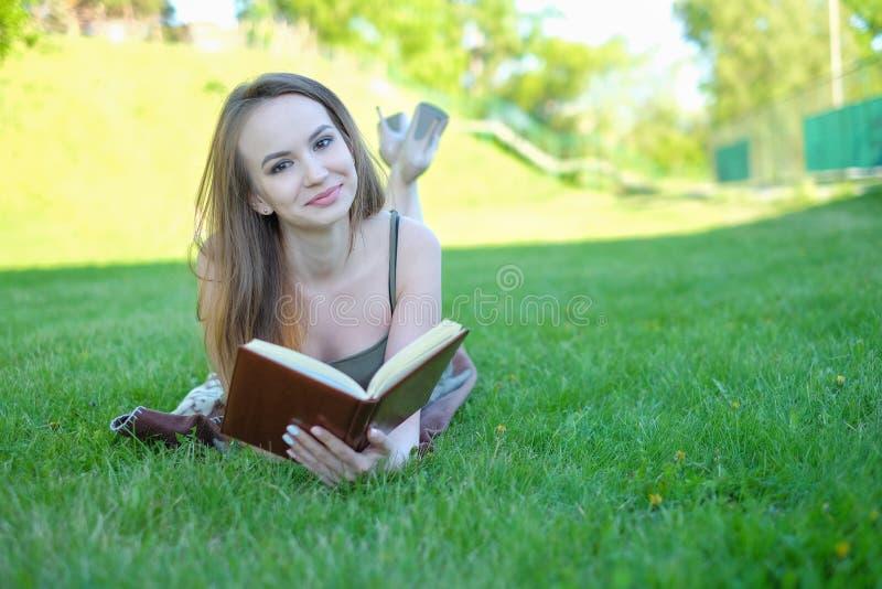 Den unga kvinnan ligger på grönt gräs och läser boken i staden parkerar arkivbild