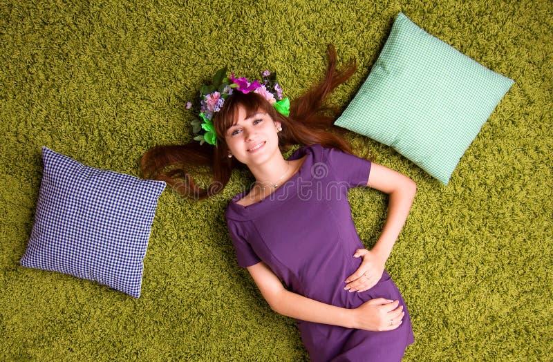 Den unga kvinnan ligger på mattan arkivfoton