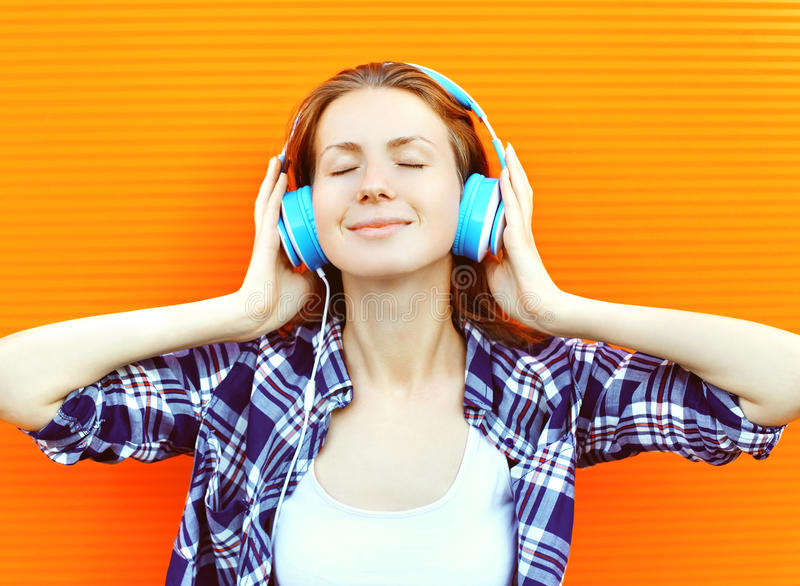 Den unga kvinnan lyssnar och tycker om den bra musiken i hörlurar arkivfoto