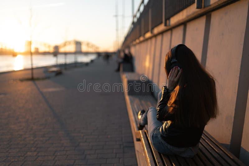 Den unga kvinnan lyssnar till musik i stängd hörlurar till och med hennes telefon som nära bär ett läderomslag och jeans på royaltyfria bilder