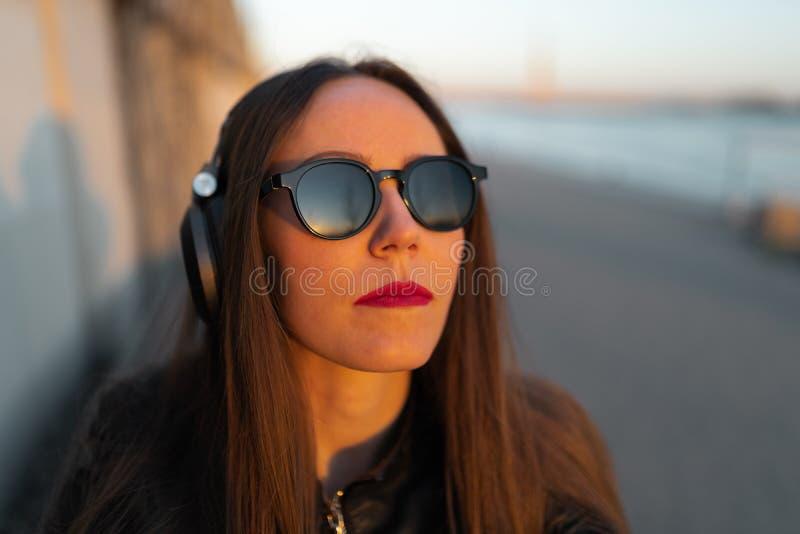 Den unga kvinnan lyssnar till musik i stängd hörlurar till och med hennes telefon som nära bär ett läderomslag och jeans på royaltyfria foton