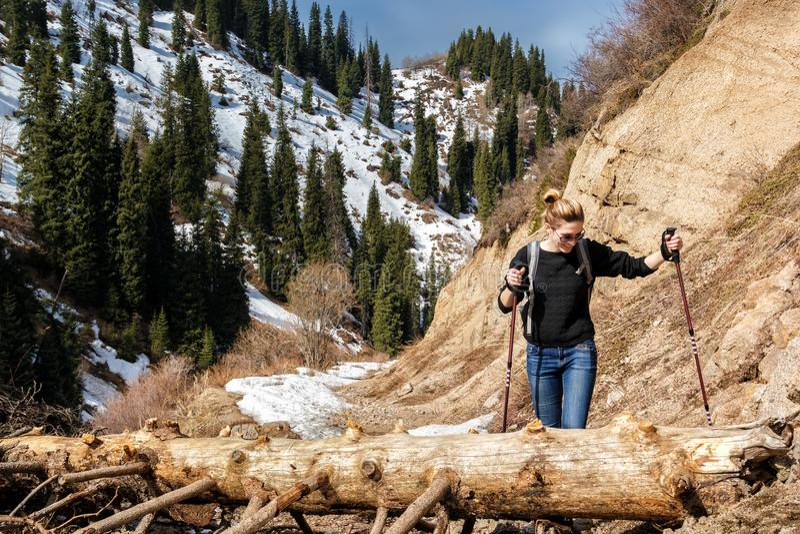 Den unga kvinnan med att gå pinnar övervinner ett hinder - ett stupat träd på en slinga arkivfoto