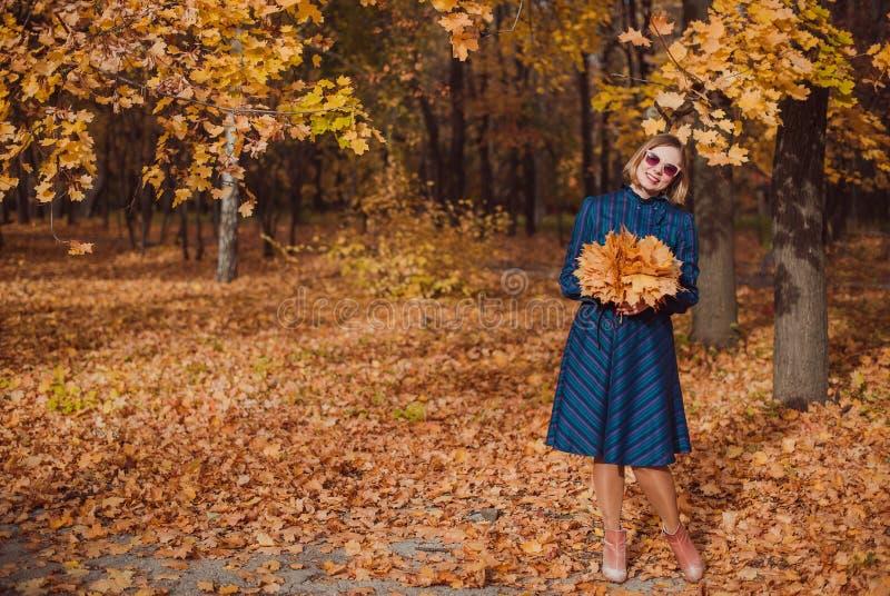 Den unga kvinnan med den bärande blåttklänningen för blont hår som går i höst, parkerar royaltyfria foton