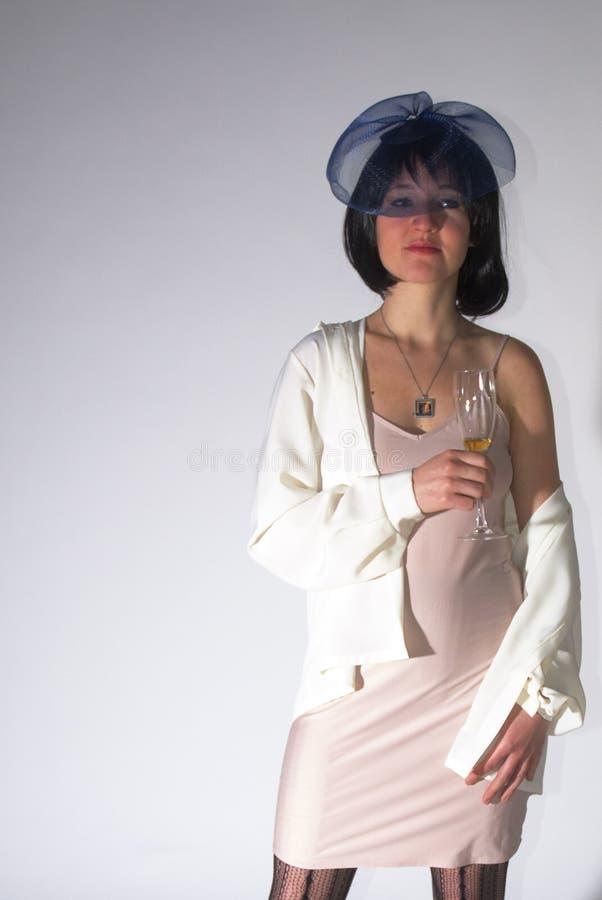 Den unga kvinnan med blått kopplar ihop hatten och champagne arkivbild