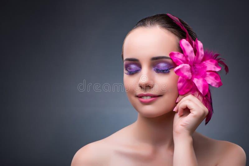 Den unga kvinnan med blommagarnering fotografering för bildbyråer
