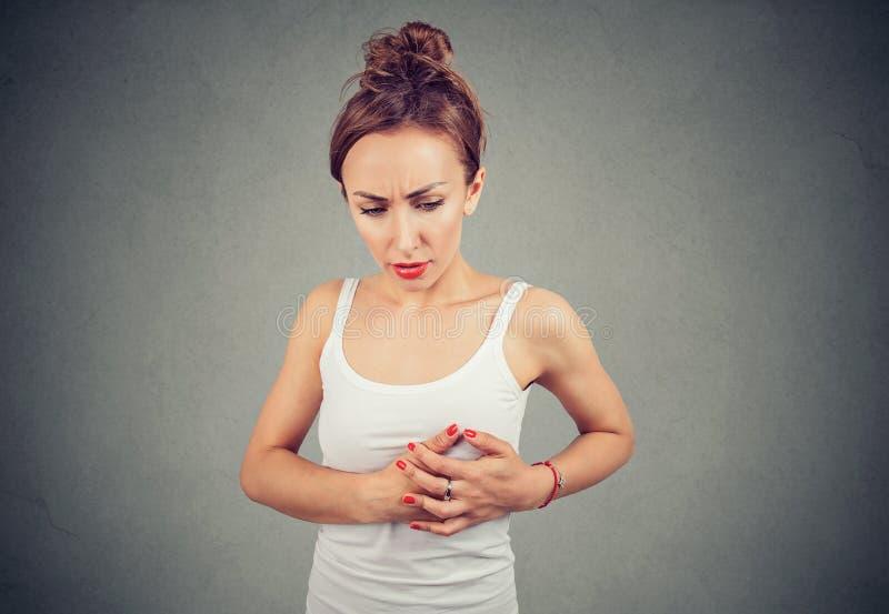 Den unga kvinnan med bröstkorgbröstet smärtar att palpera en klumpa sig arkivfoto