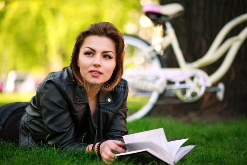 Den unga kvinnan med cykelläseboken i stad parkerar på gräset arkivfoton