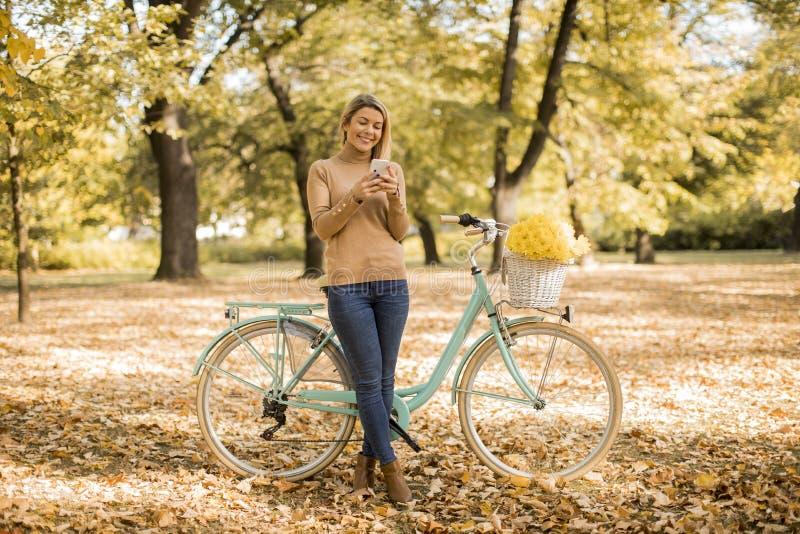 Den unga kvinnan med cykeln som anv?nder smartphonen i h?st, parkerar fotografering för bildbyråer