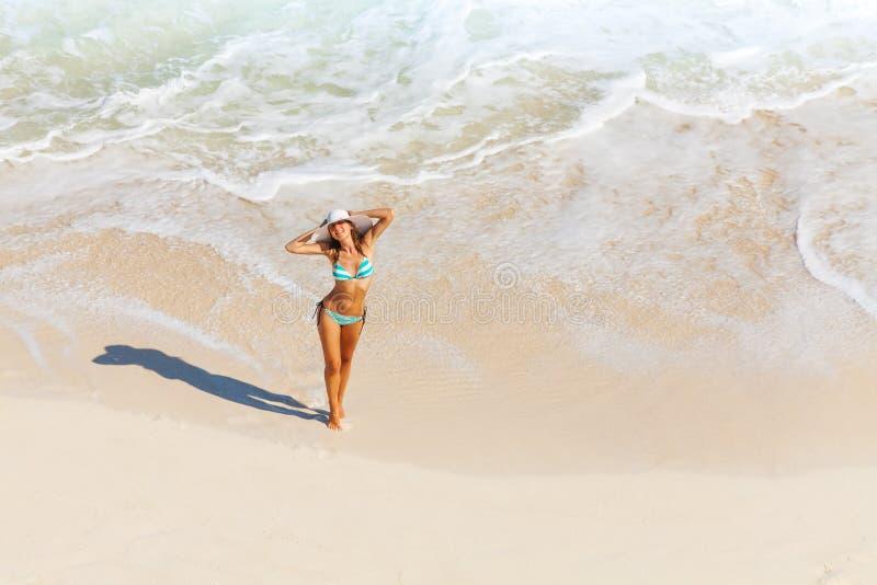Den unga kvinnan med den vita hatten står på havsand arkivbild