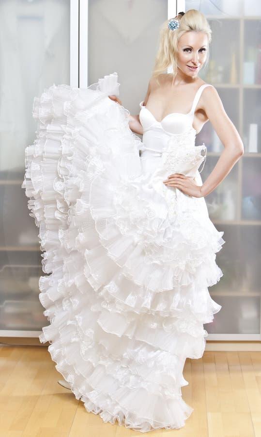 den unga kvinnan med en bröllopsklänning i händer drömmer om bröllop royaltyfria bilder