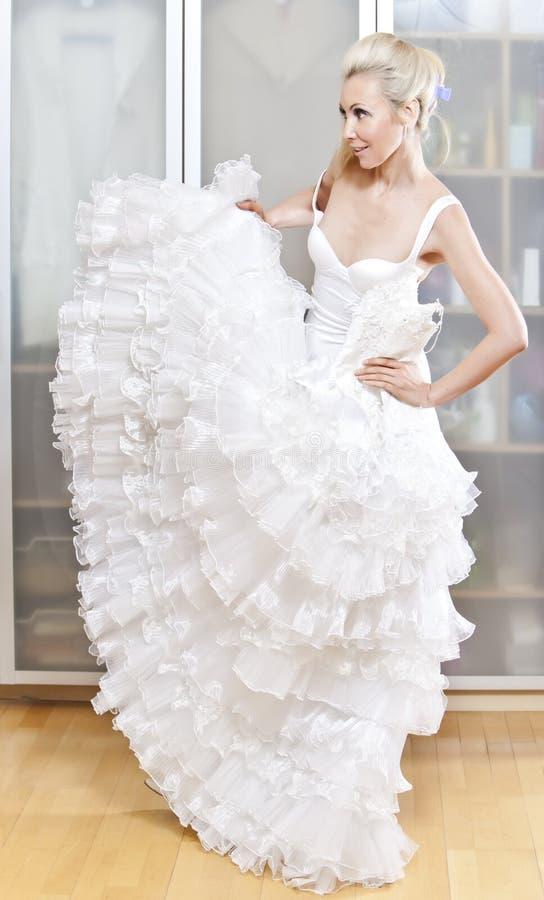 den unga kvinnan med en bröllopsklänning i händer drömmer om bröllop arkivbilder