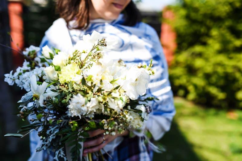 Den unga kvinnan med en härlig födelsedag blommar buketten arkivfoto