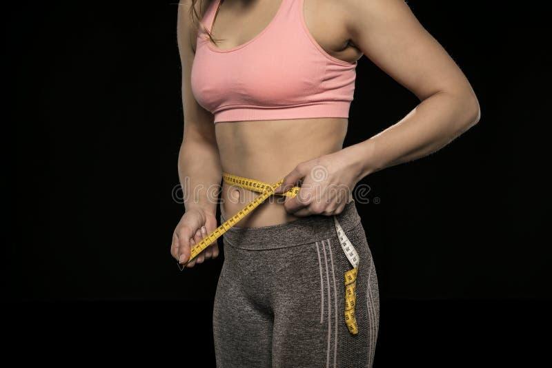 Den unga kvinnan med en idrotts- kropp använder ett mäta band arkivfoto