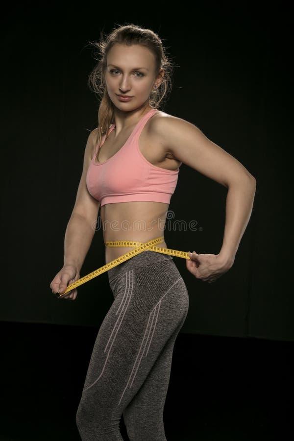 Den unga kvinnan med en idrotts- kropp använder ett mäta band royaltyfri fotografi