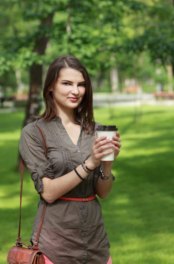 Den Unga Kvinnan Med En Kaffekopp Parkerar In Arkivbilder
