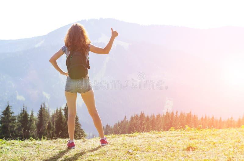 Den unga kvinnan med en ryggsäck står på överkanten av berget och visar tecknet & x22en; ok& x22; royaltyfria foton
