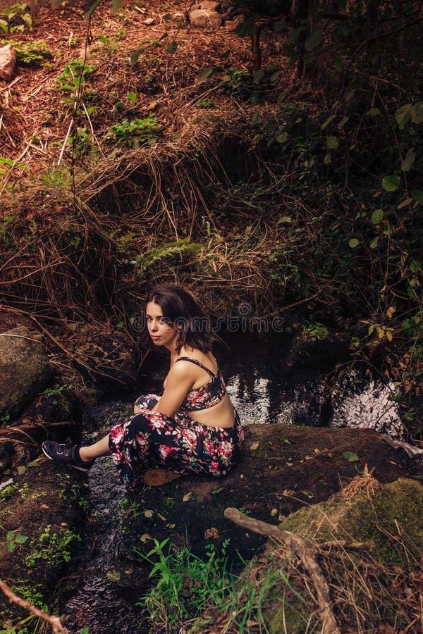 Den unga kvinnan med en trevlig klänning som sitter på, vaggar i floden arkivfoton